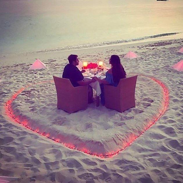 عکس عاشقانه نامزد در کنار ساحل با شمع های روشن به شکل قلب