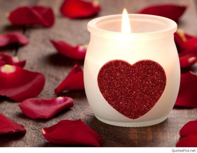 شمع قلبی در حال سوختن با گل برگ های قرمز عاشقانه