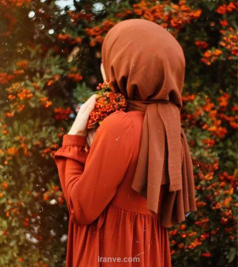 پروفایل دخترونه ایرانی با مانتو و شال قرمز با دسته گل قرمز در کنار بوته های گل قرمز
