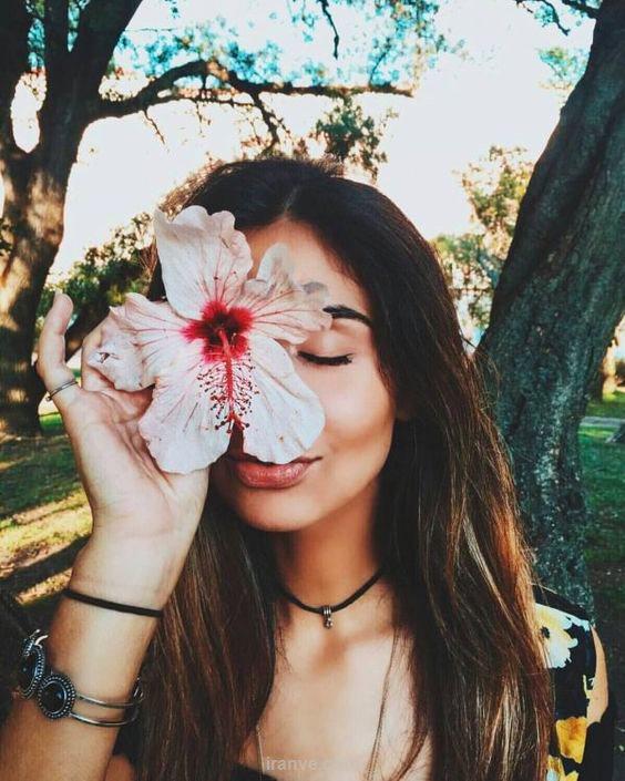 پروفایل دخترونه ی دختری که گل سفید جلوی صورتش هست