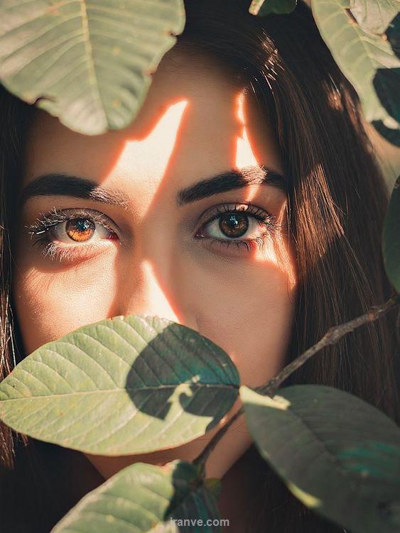 دختر چشم قهوه ای که پشت برگ درخت است