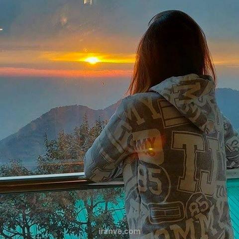 عکس پروفایل دخترونه ایستاده در کنار غروب خورشید و کوه های جنگلی